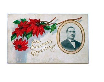 """Antique Embossed Christmas Postcard with """"Season's Greetings"""" has Red Poinsettias & Man's Portrait Postmarked 1912"""