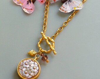 Gold necklace with flower pendant and small charms