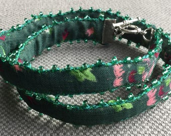 Textile bracelet, double tour, dominant of green and pink, lined with pearls of loose stones.