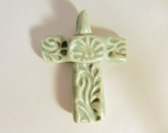 Cross pendant made of  white stoneware clay with a turquoise mat glaze
