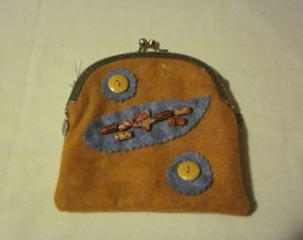 medium size change bag in rust with blue on it.  Metal clasp and fullly lined
