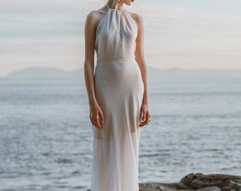Backless Sheath Wedding Dress | A simple wedding gown featuring a delicate halter neck with low back and fitted bias cut skirt with train.