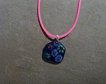 Fused glass pendant necklace, dark freeform pendant with mille fiori murini, mounted on silver plate bale,  on a pink rubber cord.