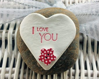 """Natural clay heart inscribed """"I love You"""" with red dotty button mounted on a pebble"""