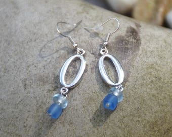 Earrings made with a silver pendant and two blue beads