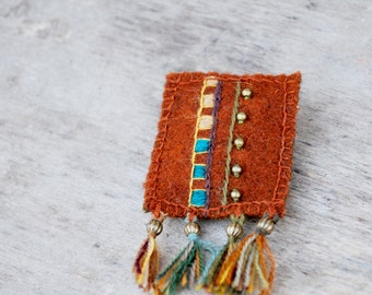 Handmade woolen textile brooch with embroidery. Rustic orange brooch with colorful embroidery and tassels. Eco friendly.