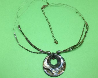 A three strand fine wire pendant necklace with small brown glass beads and a unusual brown glittery plastic disc.