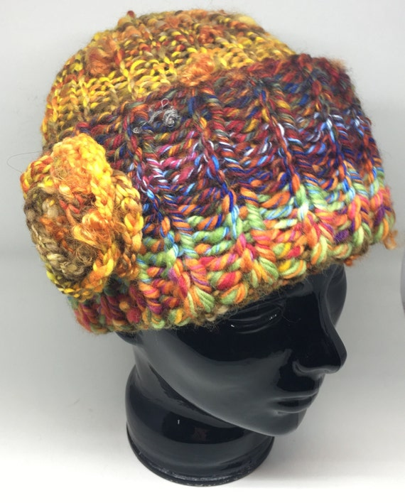 Handknit midweight winter hat made from handspun yarn of wool. Bright variegated yarn is fun to wear. Features an elegant flower detail