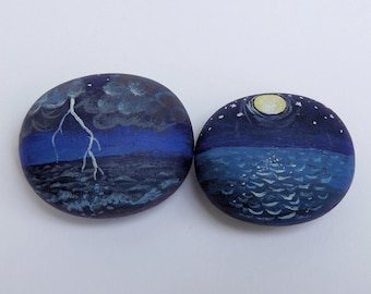 Stormy Sea, Calm Waters. Pair of matching lucky wooden pebbles painted with seascapes. Two tiny artworks, in a red velvet pouch.