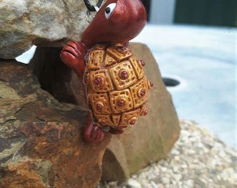 Gold and copper turtle necklace made of polymer clay.