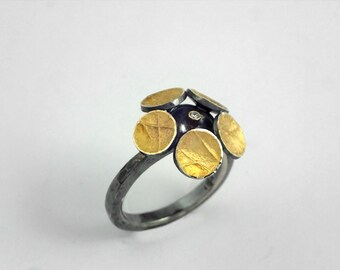 The margarita flower. A modern and stylish gold and oxidized silver ring with rough surface and a diamond.