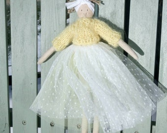 A handmade doll with a yellow mohair jumper and a frothy skirt