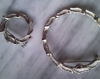 Circular silvertone brooches..with leaf pattern..raised areas in the center of each leaf..create a free flowing effect.