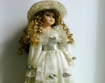 Pretty French vintage doll for decoration, period dress and ceramic / porcelain head, arms and feet, cream outfit and hat.