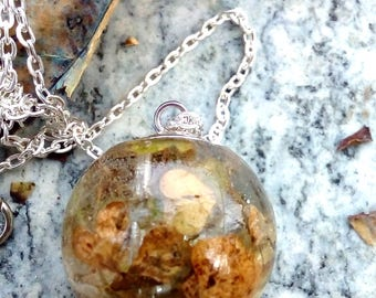 Resin ball pendant with real flowers and dried grass, with silver plated necklace.