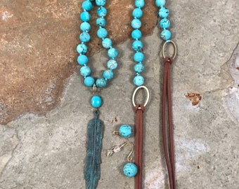 Patina bronze feather pendant on a robins egg blue howlite and leather necklace with matching earrings