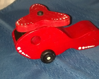 Vintage red wooden toy helicopter.