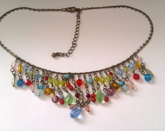 brass coloured necklace with glass and plastic beads