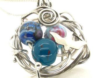 3 lampwork beads in a silver wire birds nest with silver bird on popcorn chain