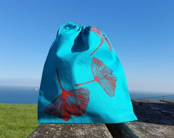 Red ginkgo leaves on turquoise bag