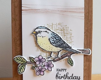 Birthday card with stamped and die cut bird on a branch, hand coloured