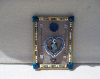 Jewelry collage art with blue rhinestone heart