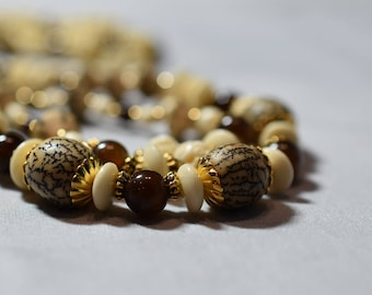 Triple strand buri nut, bone and gold necklace