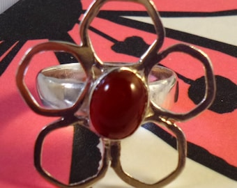 Sterling silver flower ring with an oval carnelian cabochon gemstone inset in a flower setting.