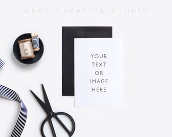 Card Mockup with stripped and pale gold ribbon, scissors and a black envelope. Styled Photography. Digital Image