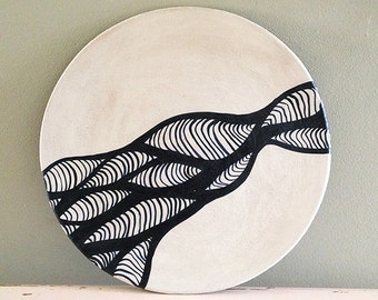 Ceramic plate, nearly black deep blue and white organic design. Waves and lines.