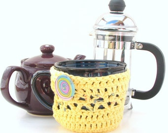 Mug Hug cozy in yellow crocheted cotton with coaster bottom and decorative buttons