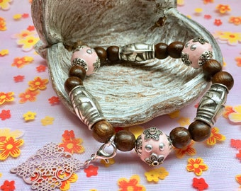 Beaded bracelet with soft pink elements and charm