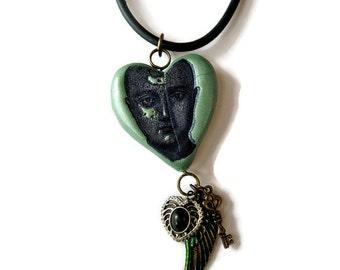 Phrenology head on polymer green pendant heart with steampunk embellishments