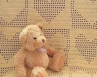 Handmade crochet baby blanket in a vanilla cream