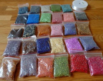 29 packets of colourful glass beads