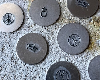 Round steel charms with a peace sign, feminist symbol, or a crown