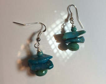 Turquoise earrings with faceted turquoise beads and a turquoise seed bead on top on sterling silver earwires.