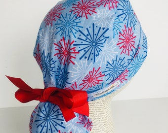 Ponytail Scrub Cap scrub hat with a light blue material with red white and blue fireworks and a matching red ribbon