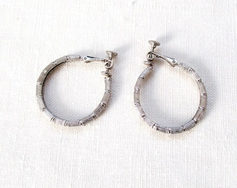 "Screw back clip earrings. Vintage Silver tone hoops. Signed Goldette. About 1.25"" diameter. In good used condition."