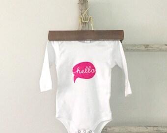 Hello. Speech bubble hello. Neon pink or white hand printed baby onesie. Screenprint baby bodysuit