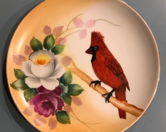 Handpainted decorative plate with flowers and a red cardinal