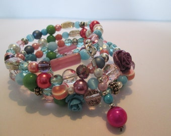 Memory wire bracelet with mix of pastel color beads and sweet dangle