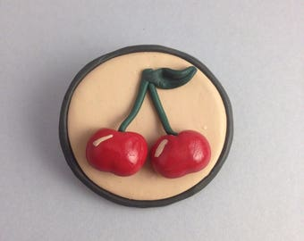 Brooch with round background and cherries