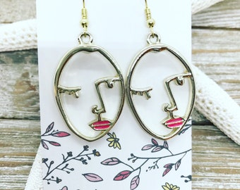 Gold tone Picasso face earrings with pink lips.