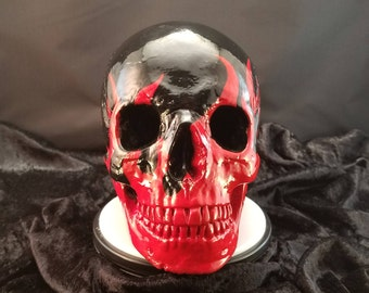 life size realistic concrete skull painted black with red flames