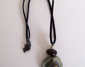 Mystical pendant with an ammonite fossil, gray and black colors.