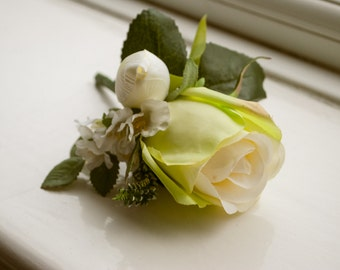 Spring buttonhole/boutonniere. Designed with an artificial cream/green rose, ivory tulip, heather and garden spray roses.