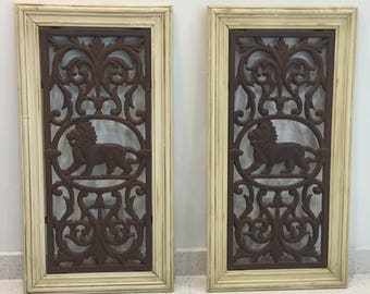 Pair of vintage iron lion wall hangings with wood frames