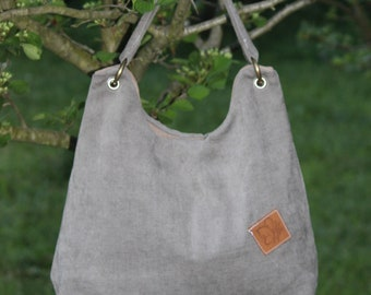 Fabric bag in grey suede leather with one free pocket and one with zipper.