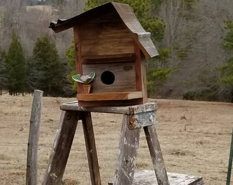 rustic handmade cedar birdhouse with old tin roof